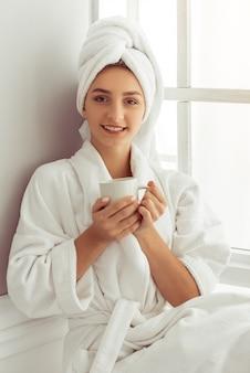 Mädchen mit einem handtuch auf dem kopf hält eine tasse