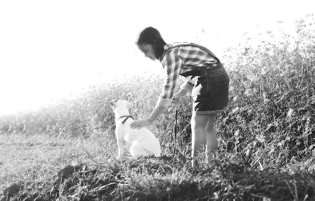 Mädchen mit einem hund auf dem gebiet der blumen.