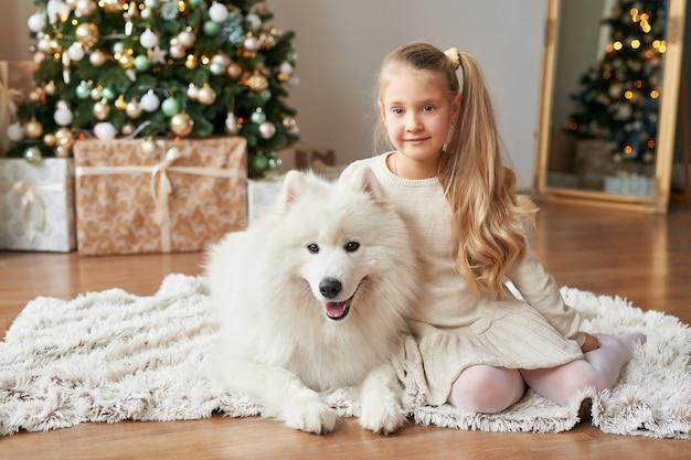 Mädchen mit einem hund nahe dem weihnachtsbaum auf dem weihnachtshintergrund