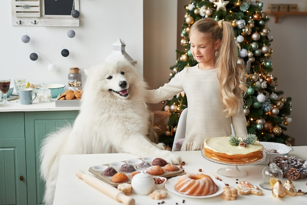 Mädchen mit einem hund nahe dem weihnachtsbaum in weihnachten