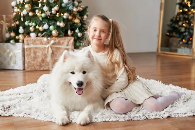 Mädchen mit einem hund nahe dem weihnachtsbaum