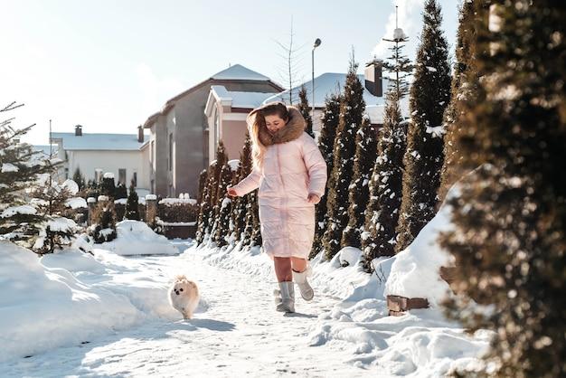 Mädchen mit einem hundewelpenspitz, der im winter im freien spaß spielt
