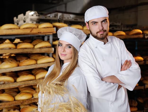 Mädchen mit einem kerl im weißen overall in der bäckerei
