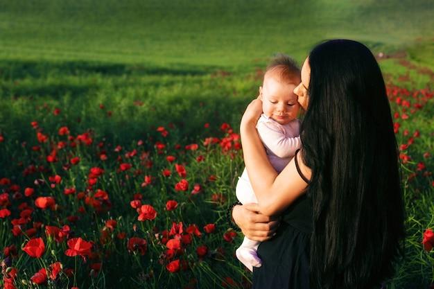 Mädchen mit einem kind in einem mohnfeld