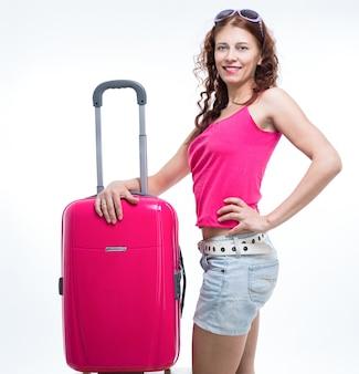 Mädchen mit einem koffer, der auf weißem hintergrund unterwegs ist
