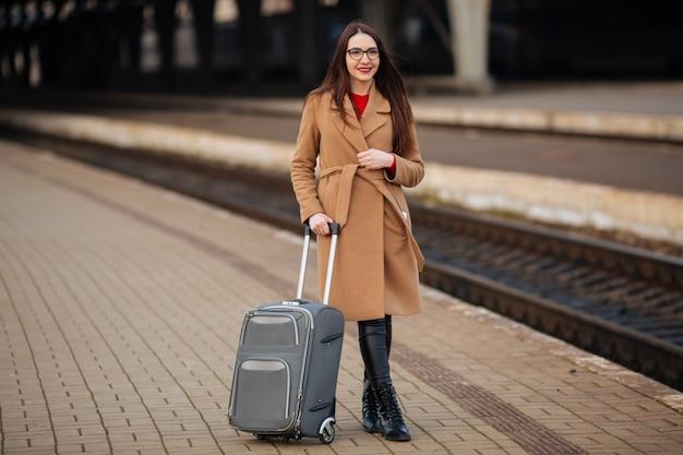 Mädchen mit einem koffer reist. auf der suche nach einem bus am bahnhof.