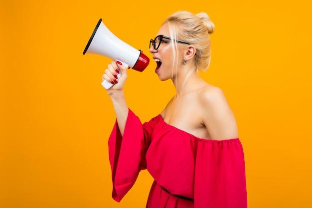 Mädchen mit einem lautsprecher steht seitlich auf einem gelben studiohintergrund