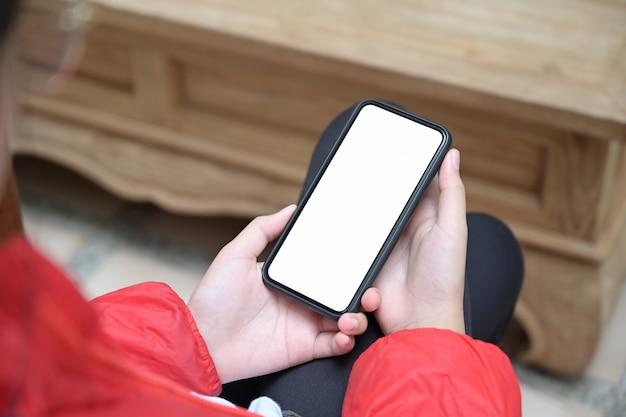 Mädchen mit einem mobilen smartphone des leeren bildschirms in ihren händen