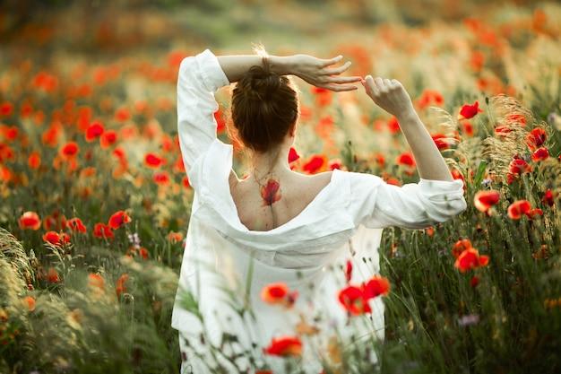 Mädchen mit einem nackten rücken mit einem tattoo darauf hält hände über einem kopf und dem schönen mohnfeld