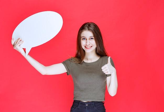 Mädchen mit einem ovalen info-board, das daumen nach oben zeigt.