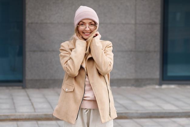 Mädchen mit einem rosa bennie, das glücklich auf der straße lächelt