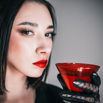 Mädchen mit einem roten glas. einen cocktail trinken.