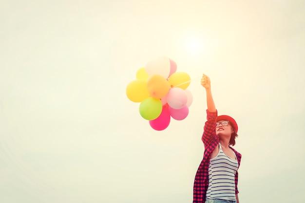 Mädchen mit einem roten hut und luftballons