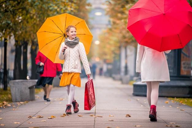 Mädchen mit einem roten und gelben regenschirm treffen sich auf der herbststraße der stadt. unter ihren füßen wird das trockene laub genäht.