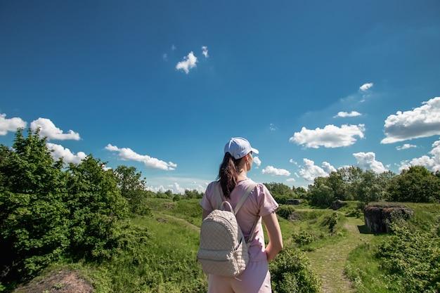 Mädchen mit einem rucksack auf dem hintergrund einer schönen landschaft.