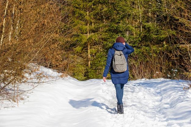 Mädchen mit einem rucksack, der in einem schneebedeckten wald steht.