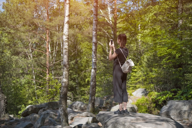 Mädchen mit einem rucksack im wald fotografierte auf einem smartphone. rückansicht
