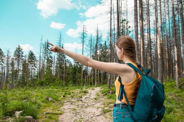 Mädchen mit einem rucksack schüttelt seine hand zur seite und geht in den wald, genießt die schönen hügel an einem sonnigen tag.