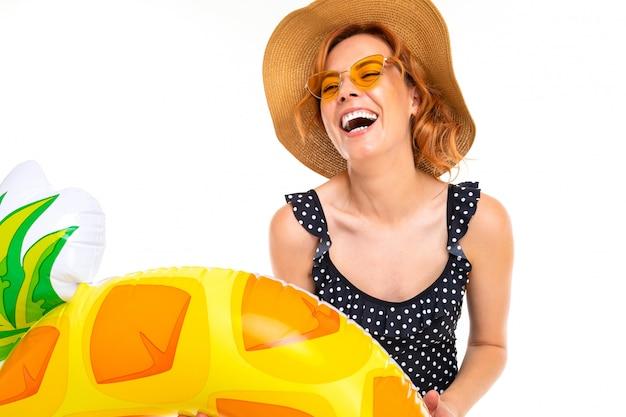 Mädchen mit einem schönen lächeln gekleidet in einem retro-badeanzug und einem strohhut hält einen schwimmkreis in der form der ananas auf einer weißen wand