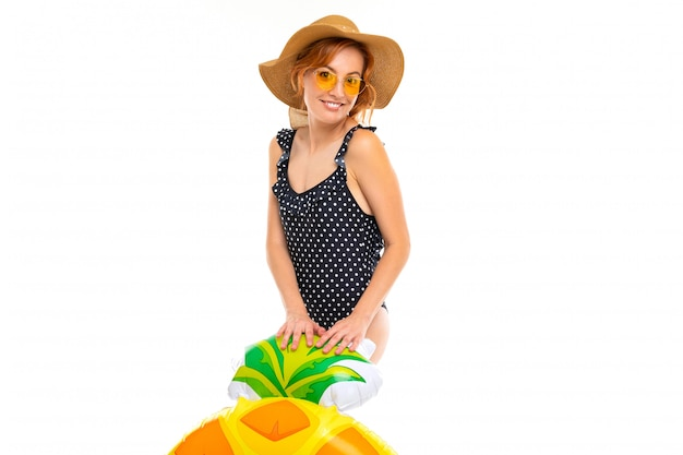 Mädchen mit einem schönen lächeln, gekleidet in einen schwarzen einteiligen retro-badeanzug und einen strohhut, hält einen schwimmkreis in form einer ananas an einer weißen wand