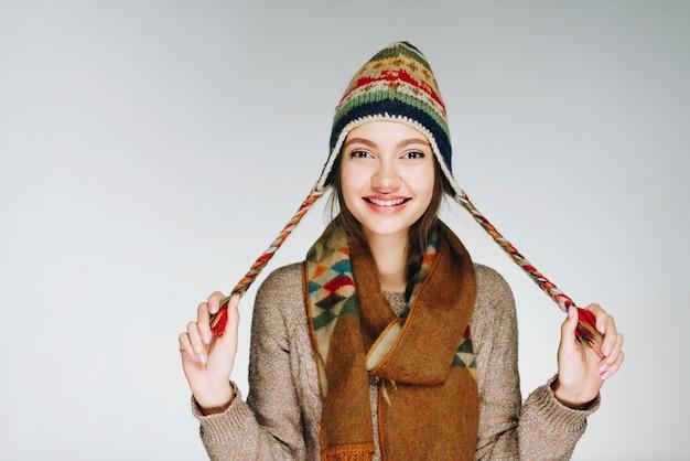Mädchen mit einem schönen lächeln in einem hut, der spielerisch aufwirft