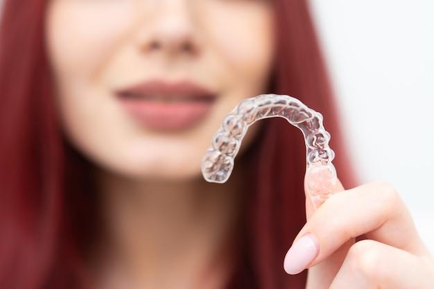 Mädchen mit einem schönen lächeln zeigt einen transparenten mundschutz
