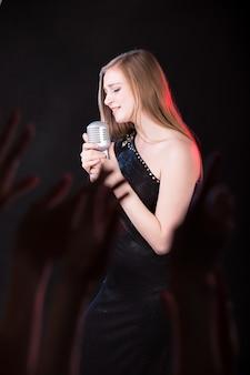 Mädchen mit einem schwarzen kleid singt