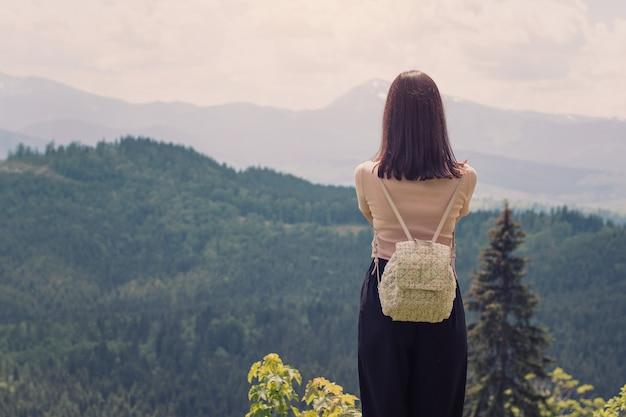 Mädchen mit einem stehenden hintergrund des rucksacks von bergen und von wäldern. rückansicht. sonniger sommertag