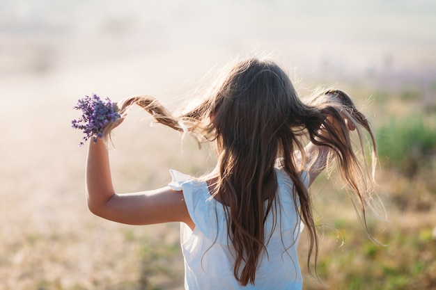 Mädchen mit einem strauß lavendel glättet die haare von hinten
