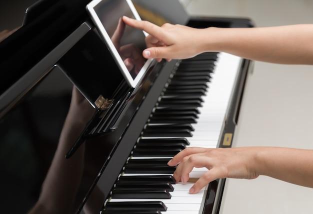 Mädchen mit einem tablet zu lernen, das klavier zu spielen