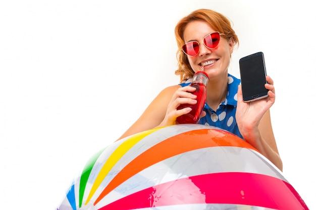 Mädchen mit einem telefon mit einem modell an einer weißen wand