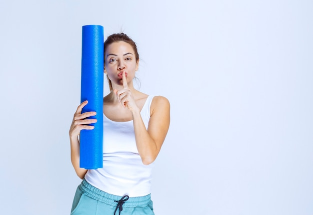 Mädchen mit einer blauen yogamatte, die um ruhe bittet.