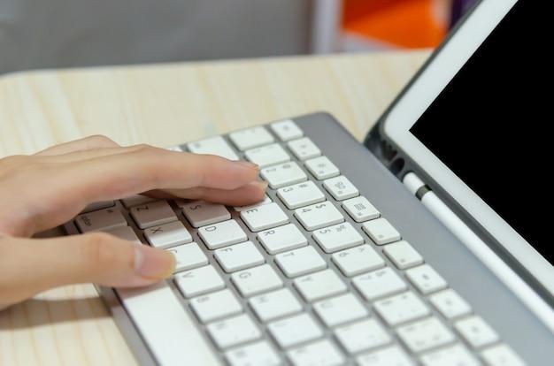 Mädchen mit einer computertastatur. online zu hause studieren. computerspiele und soziale medien spielen.
