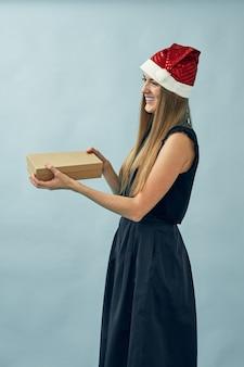 Mädchen mit einer geschenkbox in ihren händen und einem weihnachtsmannhut tragend
