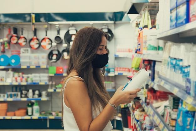 Mädchen mit einer gesichtsmaske, die artikel am supermarkt kauft