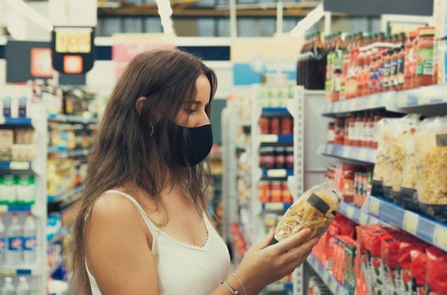 Mädchen mit einer gesichtsmaske, die artikel im supermarkt sucht und kauft.