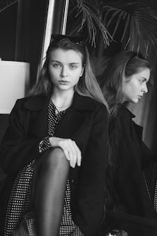 Mädchen mit einer kamera in einem café, schwarz und weiß