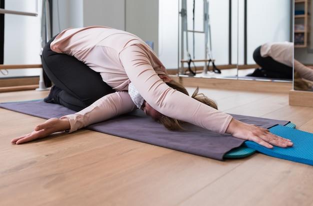 Mädchen mit einer maske, die sich in einem pilates-kurs auf einer matte den rücken streckt