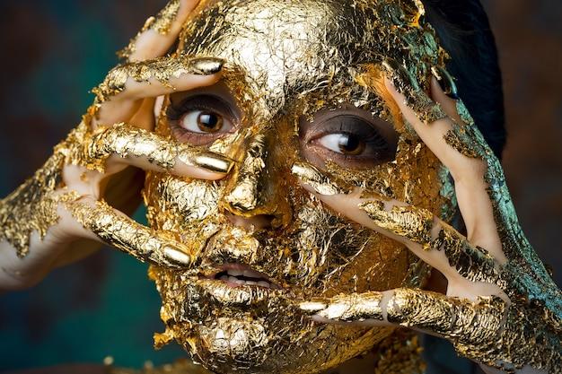 Mädchen mit einer maske im gesicht aus blattgold düsteres studioporträt einer brünette