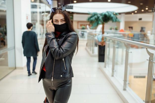 Mädchen mit einer medizinischen schwarzen maske geht entlang eines einkaufszentrums. coronavirus pandemie. mädchen in einer schutzmaske kauft im einkaufszentrum ein
