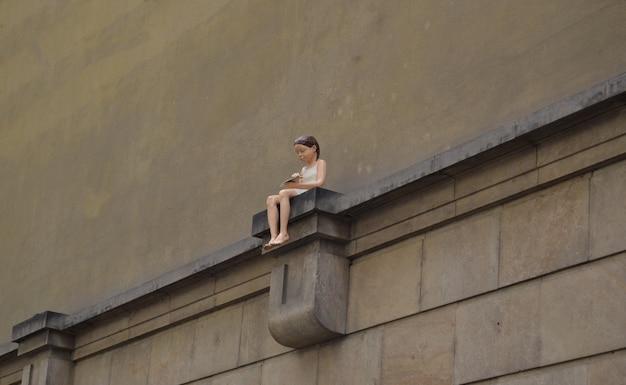 Mädchen mit einer papierfläche, die auf einem sockel auf einer wand sitzt