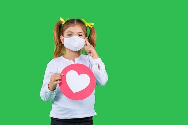 Mädchen mit einer schutzmaske, die einen kreis mit einem roten herzen auf einem grünen isolierten hintergrund hält