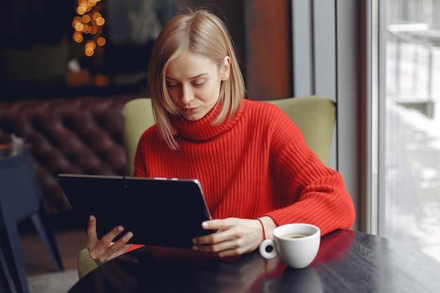 Mädchen mit einer tablette. frau in einem café. dame sitzt am tisch.