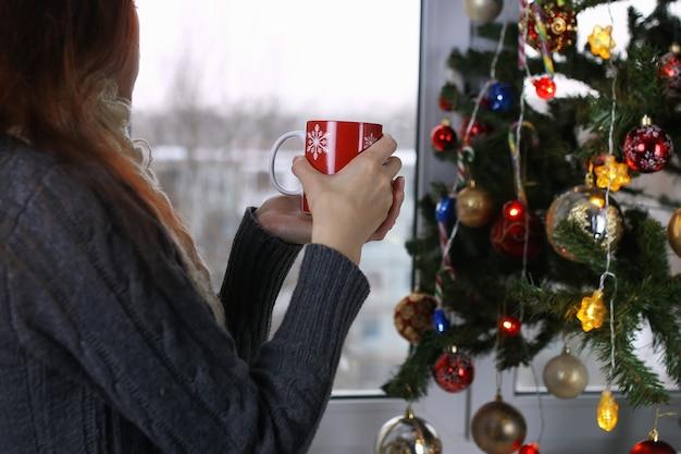 Mädchen mit einer tasse heißgetränk steht in der silvesternacht vor einem fenster