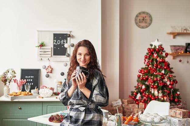 Mädchen mit einer tasse in der neujahrsküche