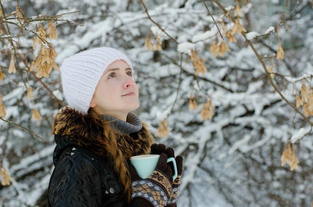 Mädchen mit einer tasse tee im freien zwischen den bäumen, die nach oben schauen
