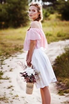 Mädchen mit einer weidentasche und blumen auf der natur. sommer und hitze