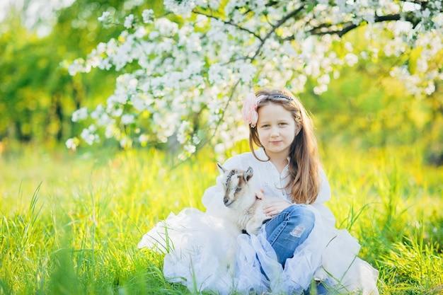 Mädchen mit einer ziege, die im gras in einem üppigen apfelgarten sitzt