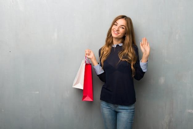 Mädchen mit einkaufstaschen begrüßend mit der hand mit glücklichem ausdruck