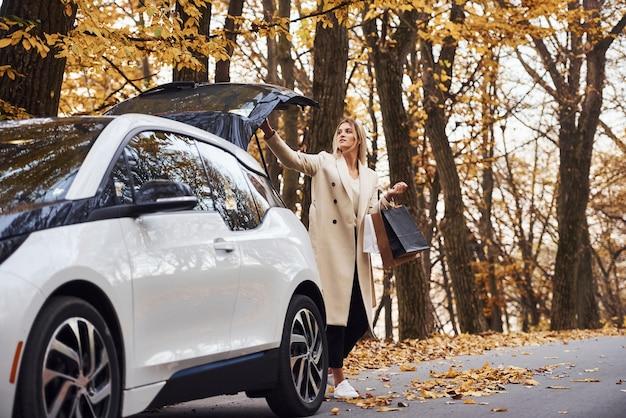 Mädchen mit einkaufstüten in den händen haben eine herbstreise mit dem auto. modernes brandneues auto im wald.